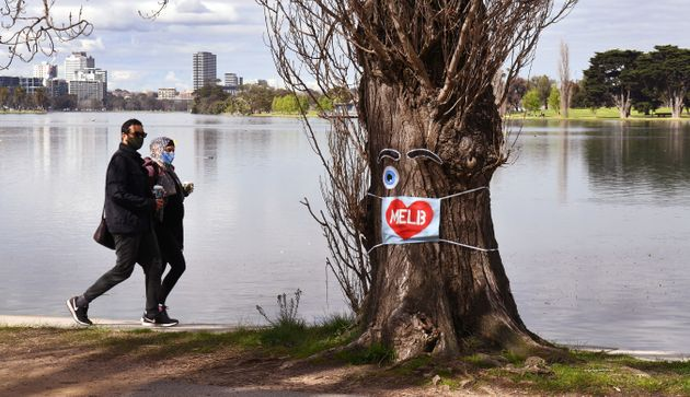 People wearing face masks exercise around the Albert Park Lake in Melbourne on August 26, 2020, as the...