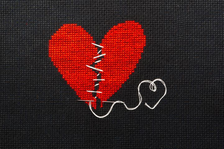 Two halves heart embroidered red thread on black fabric. Two halves heart sewn with black thread.