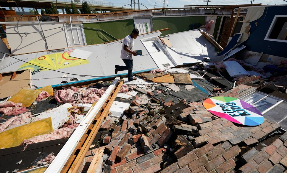 Benjamin Luna helps recover items from the children's wing of the First Pentecostal Church that was destroyed by Hurricane La
