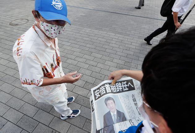아베 총리의 사임 뉴스를 실은 아사히 호외판을 받아드는 일본 시민의