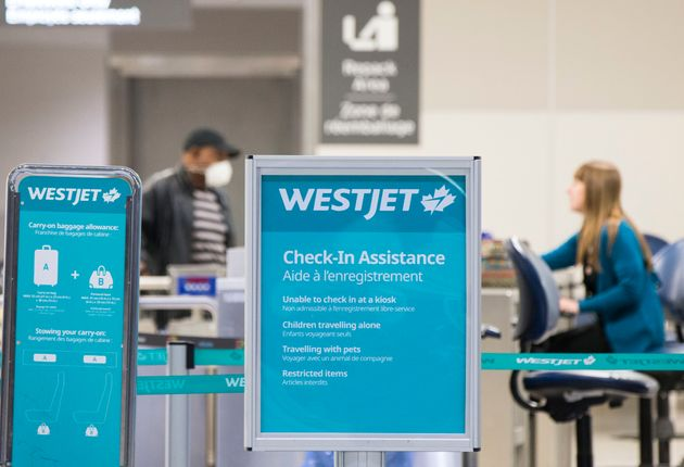 A traveller checks in at the WestJet in Toronto, March 24, 2020. The airline has introduced zero tolerance...