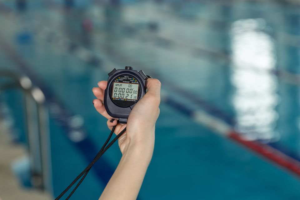 Close-up of coach hand holding stopwatch at
