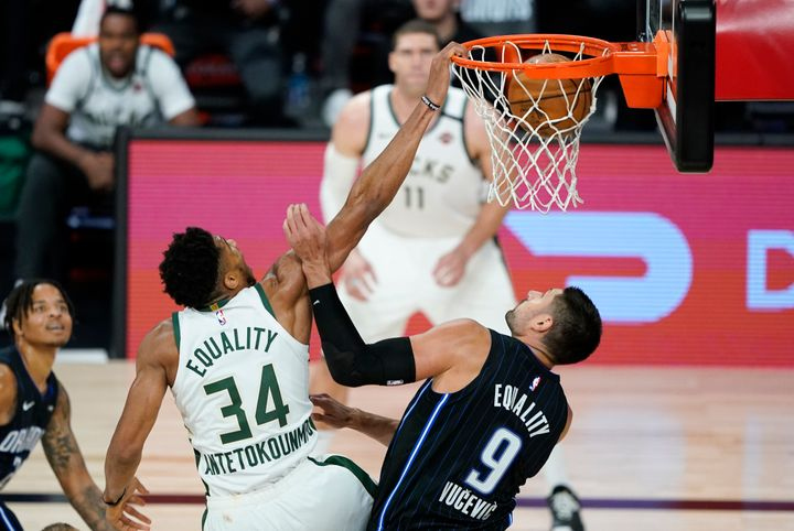 Milwaukee Bucks' Giannis Antetokounmpo dunks the ball over Orlando Magic's Nikola Vucevic during the second half of an NBA basketball game on Aug. 24, 2020, in Lake Buena Vista, Florida.