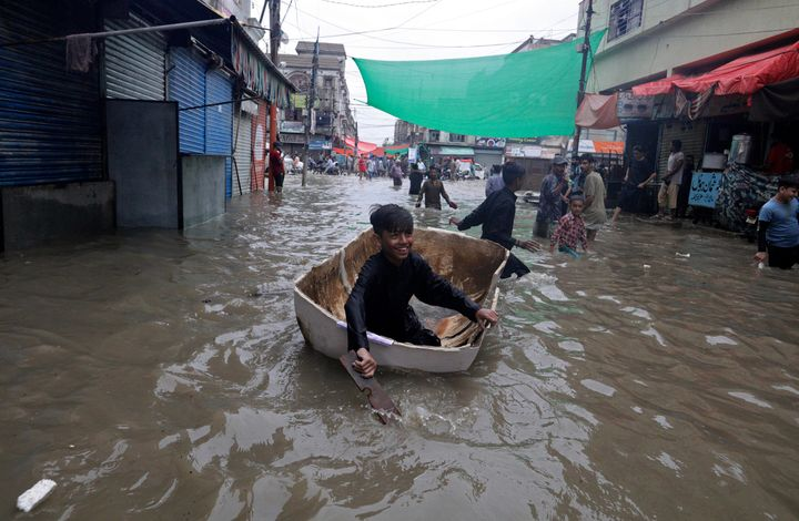 A boy uses half of a fiber tank to navigate a flooded street after heavy monsoon rains, in Karachi, Pakistan, Thursday, Aug.