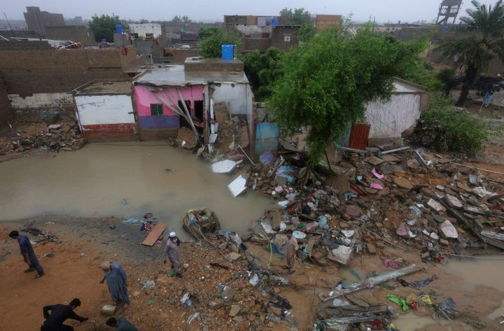 Local residents gather beside their damaged houses caused by heavy monsoon rains, in Yar Mohammad village near Karachi, Pakis