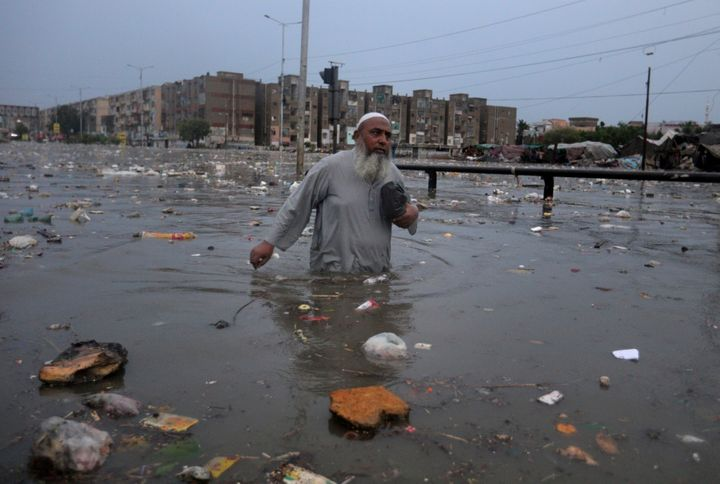 A man wades through a flooded road after a heavy rainfall in Karachi, Pakistan, Friday, Aug. 21, 2020.