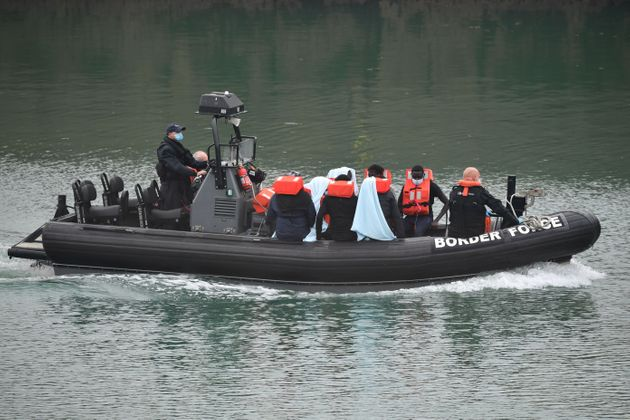 UK Border Force officials transfer migrants in a patrol vessel after they were intercepted while travelling...
