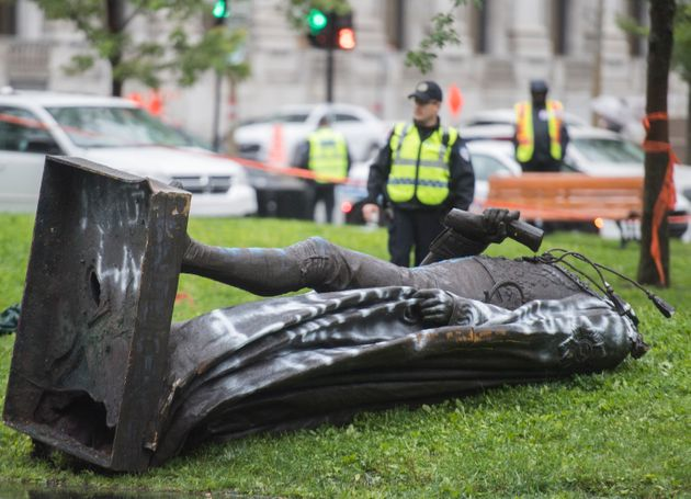 Police officers are shown at the scene next to the statue of Sir John A. MacDonald after it was torn...