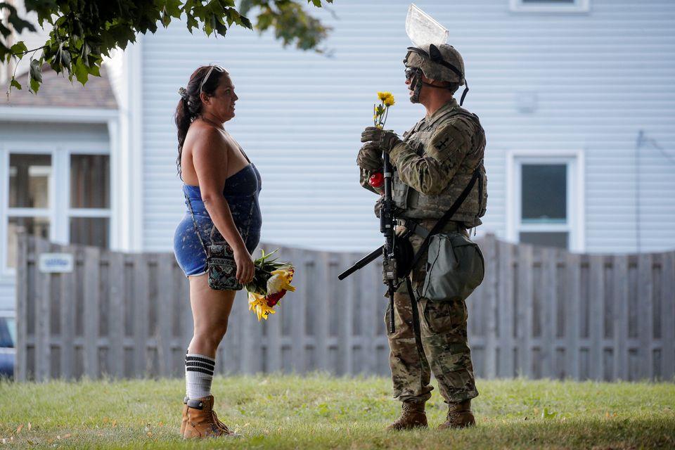 한 여성이 시위 진압을 위해 투입된 한 위스콘신 주방위군 군인에게 꽃을 건네고 있다.커노샤, 위스콘신주. 2020년