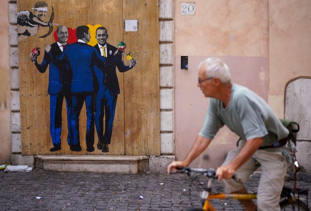 A man cycles past a graffitti by Italian street artist TvBoy shows from left former Premier Matteo Renzi,...