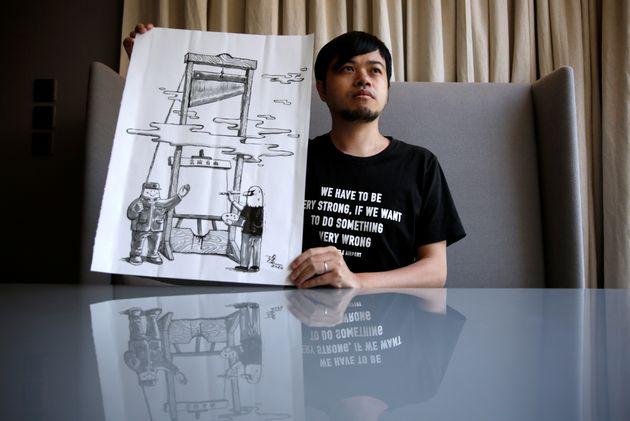 作品「ギロチン」と一緒にカメラにうつる時事漫画家の阿塗さん=2020年7月28日、ロイター通信