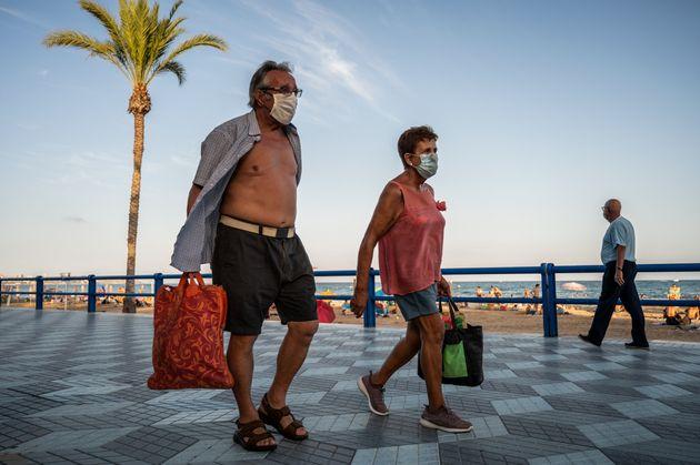 Una pareja con máscara, en una playa de