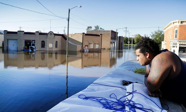 Cory Harrison stands on a floodwall as he looks over businesses flooded by the Cedar River on Sept. 27,...