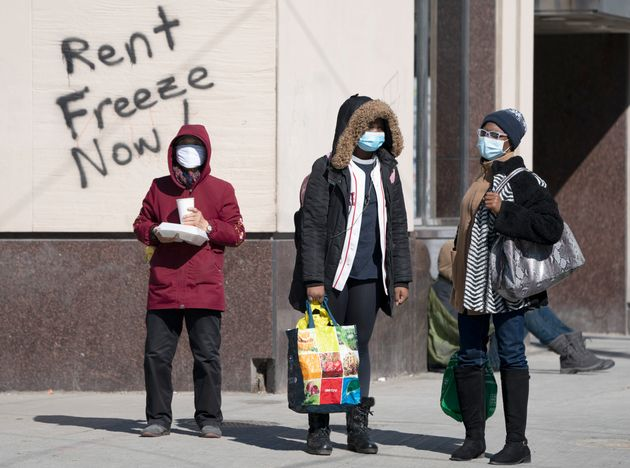 Masked pedestrians wait at a crosswalk in front of graffiti demanding a rent freeze, in Toronto on Thursday,...
