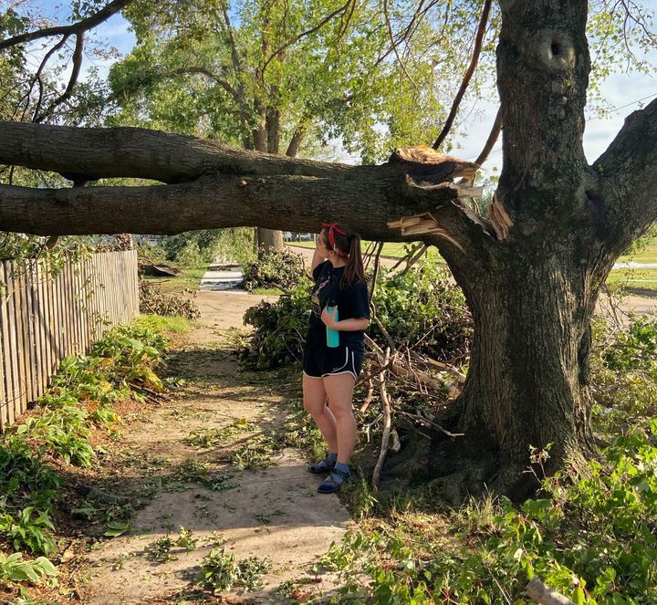 The writer stands by a tree in her Cedar Rapids, Iowa, neighborhood damaged by a Category 4 windstorm called a derecho in ear