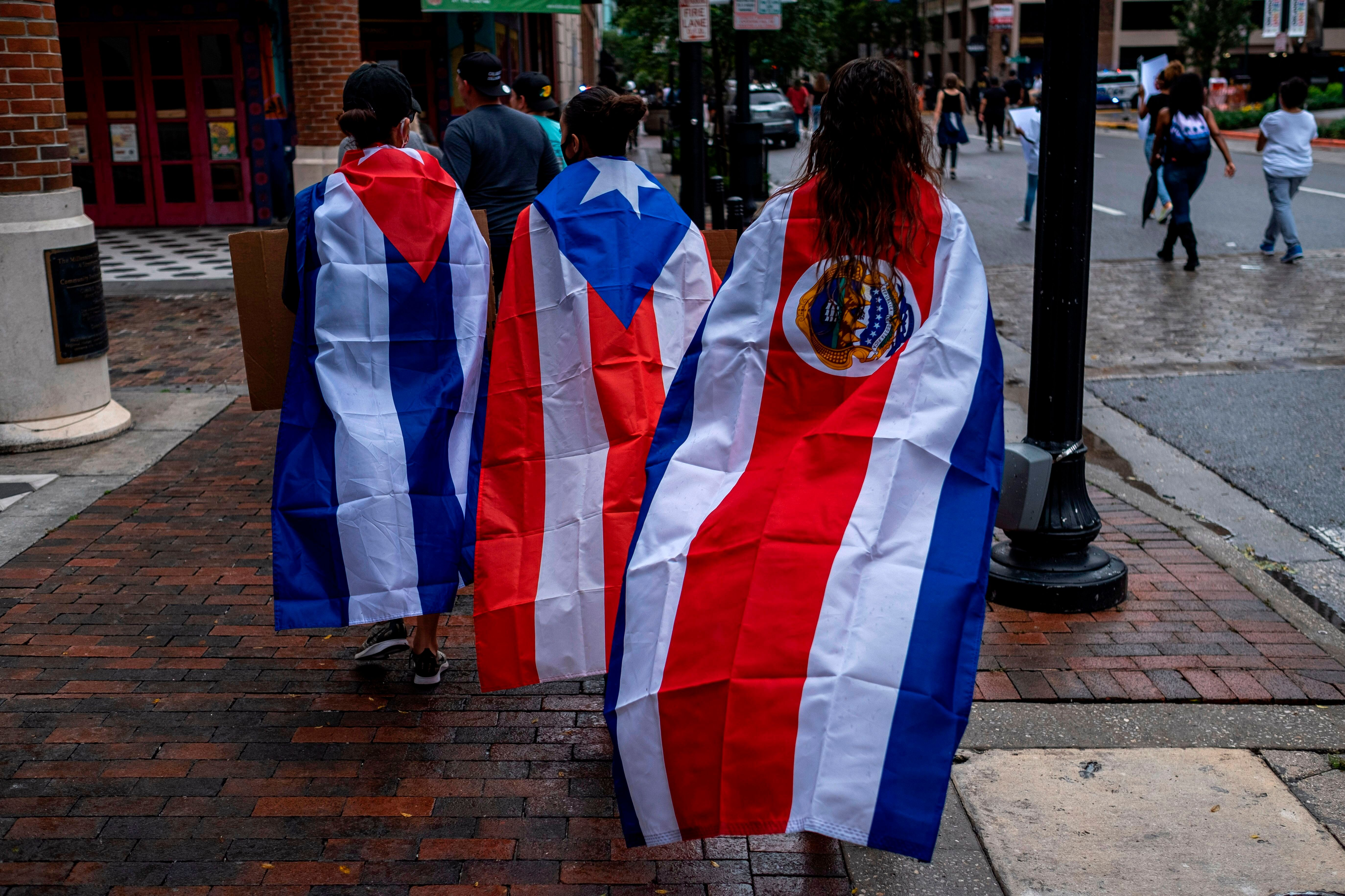 """Protesters wear Cuban, Puerto Rican and Costa Rican flags during an anti-racist protest in Orlando, Florida, after the killing of George Floyd this spring. While Trump has accused Joe Biden of favoring radical """"socialism"""" and fomenting unrest, the Biden campaign has begun to compare Trump's response to the protests to the authoritarian tendencies of the Latin American leaders the U.S. president claims to oppose."""