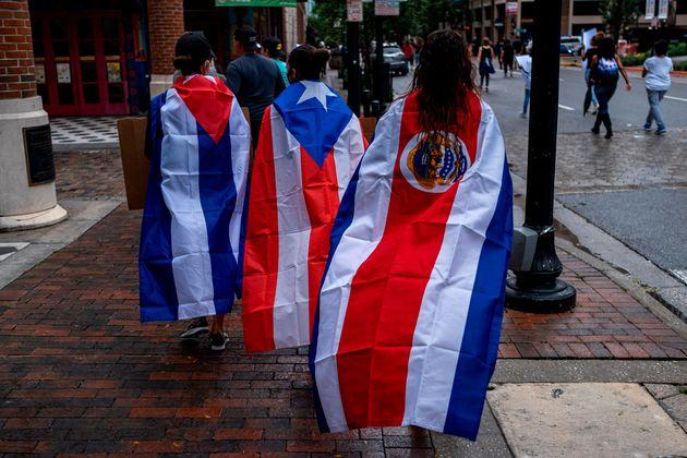 Des manifestantes arborent les drapeaux cubain, portoricain et costaricain lors d'une marche antiraciste...