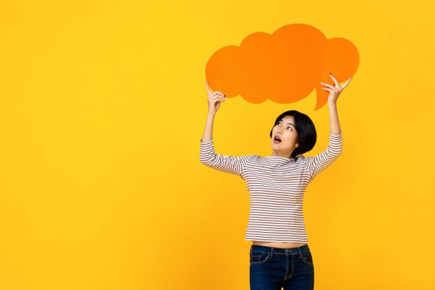Young Asian woman in casual clothes holding empty speech bubble in colorful yellow studio