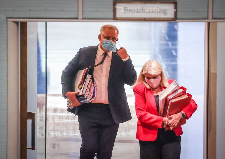 Australian Prime Minister Scott Morrison removes his face mask as he enters the House of Representatives for Question Time at Parliament House on September 2, 2020 in Canberra, Australia.