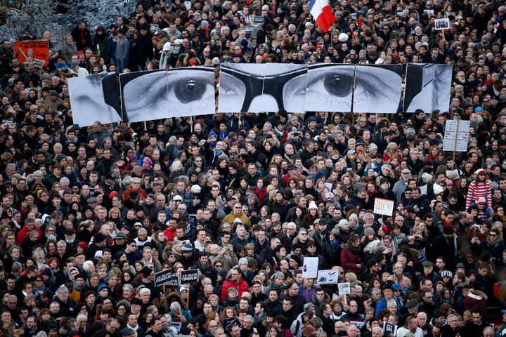 """People hold panels to create the eyes of late Charlie Hebdo editor Stephane Charbonnier, known as """"Charb,"""" as hundreds of tho"""