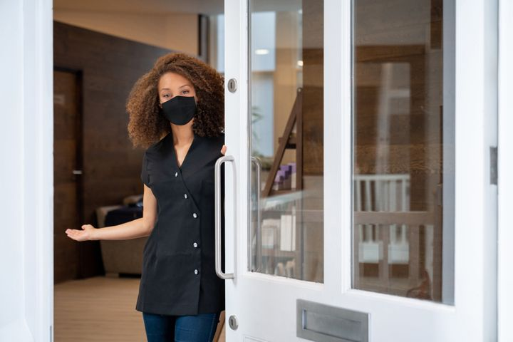Business owner opening the door of her spa wearing a facemask.
