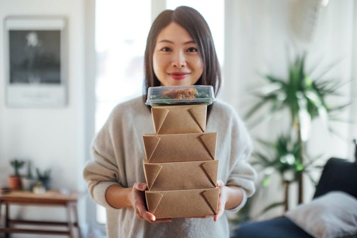 Close up shot of smiling young woman holding a stack of delivery food boxes for sharing.