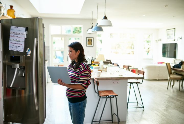 Woman at home in kitchen, checking fresh food and buying groceries online.
