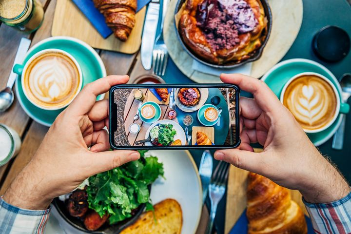 Man photographing breakfast in a cafe with smartphone