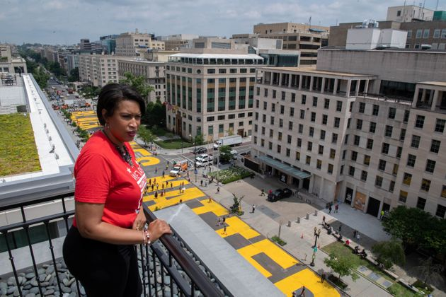 Mayor Muriel Bowser looks out over a Black Lives Matter sign that was painted during anti-racism protests...
