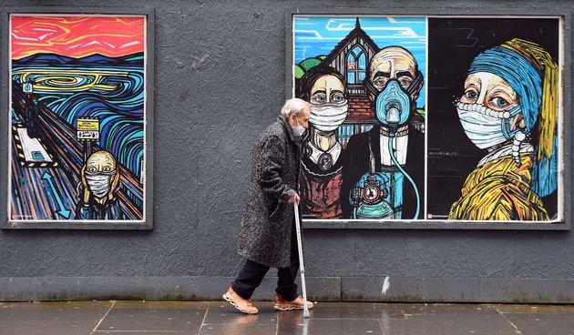 Un passant portant un masque marche devant des œuvres d'art célèbres revisitées...