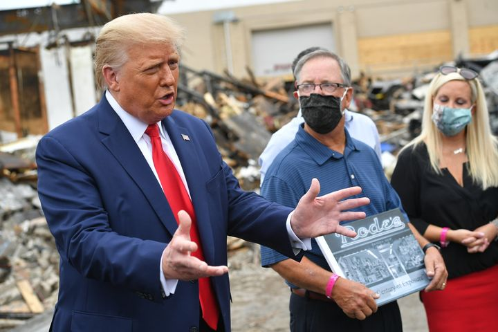 President Donald Trump, flanked by John Rode III, the former owner of Rode's Camera Shop, speaks with the press during