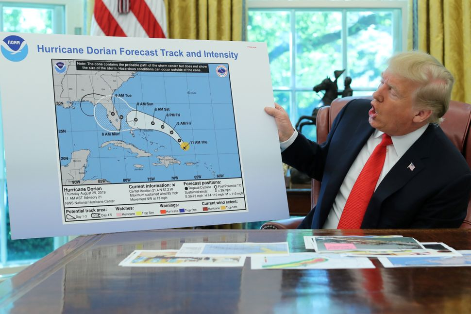 In the Oval Office of the White House, President Donald Trump holds a chart showing the original projected track of Hurricane