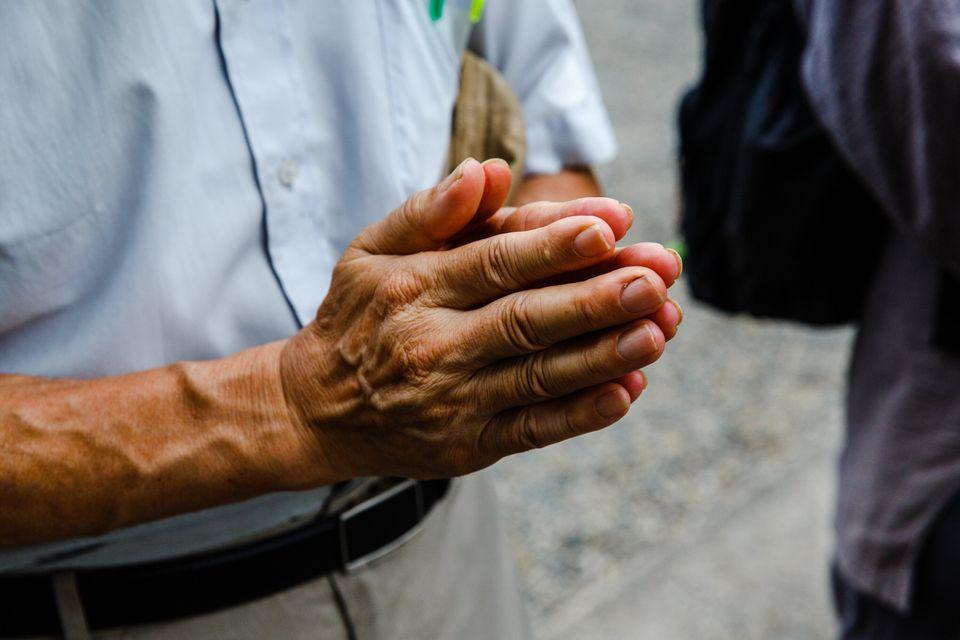 黙祷中に手を合わせる男性