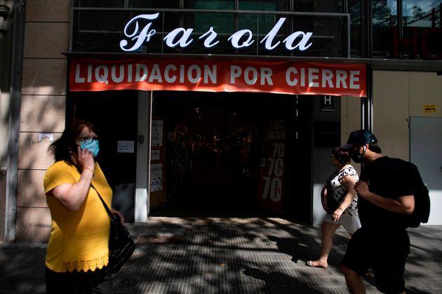 Un grupo de personas pasea por delante de un negocio cerrado por la crisis del coronavirus, en