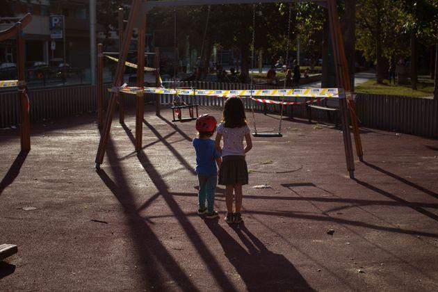 Imagen de archivo de dos niños frente a un columpio precintado en Barcelona debido a la pandemia...