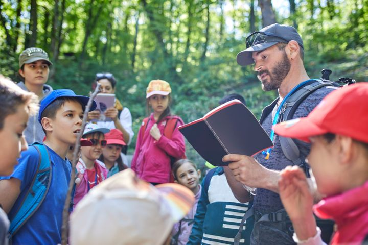 A stock photo of a man reading to kids on a field trip in forest.