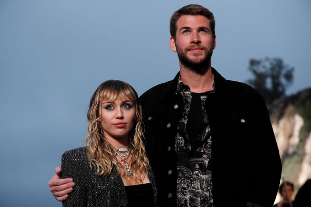 Miley Cyrus and Liam Hemsworth, then married, pose at the Saint Laurent Men's Spring/Summer 2020...