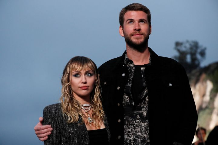 Miley Cyrus and Liam Hemsworth, then married, pose at the Saint Laurent Men's Spring/Summer 2020 fashion show on June 6