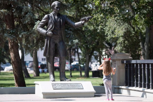 A little girl stops to look at a statue of John A. Macdonald in Victoria Park in Regina on August, 22,...