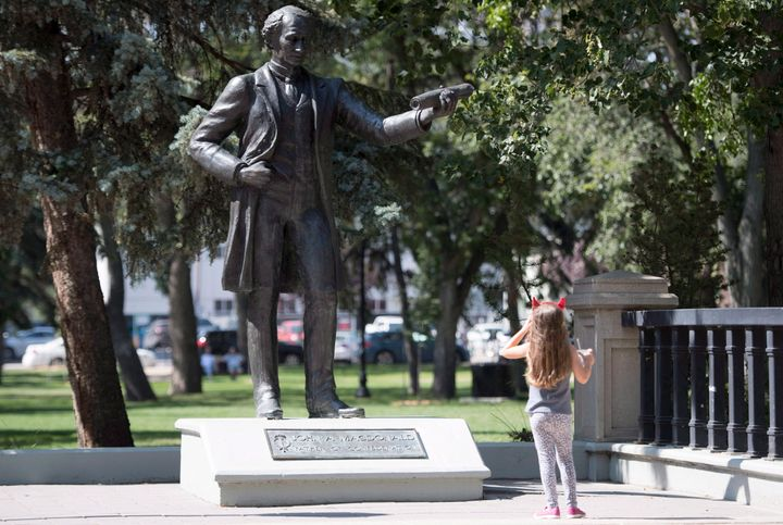 A little girl stops to look at a statue of John A. Macdonald in Victoria Park in Regina on August, 22, 2018. THE CANADIAN PRESS J