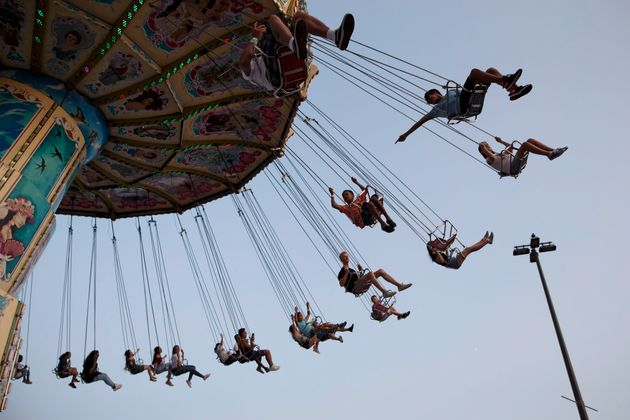 Children swing on a midway ride at the 140th annual Canadian National Exhibition in Toronto on Aug. 19,