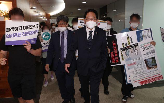 4일 서울 회현동 건강증진개발원에서 열린 정부 여당과 의료계의 공공의료 확충 정책 관련 협상 서명식장 앞에서 전공의들이 졸속 합의에 반대하며 피켓시위를 벌이고