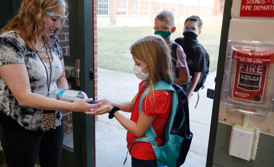 초등학생들이 교실에 들어가기 전 손소독을 하고 있다. 고들리, 텍사스주, 미국.