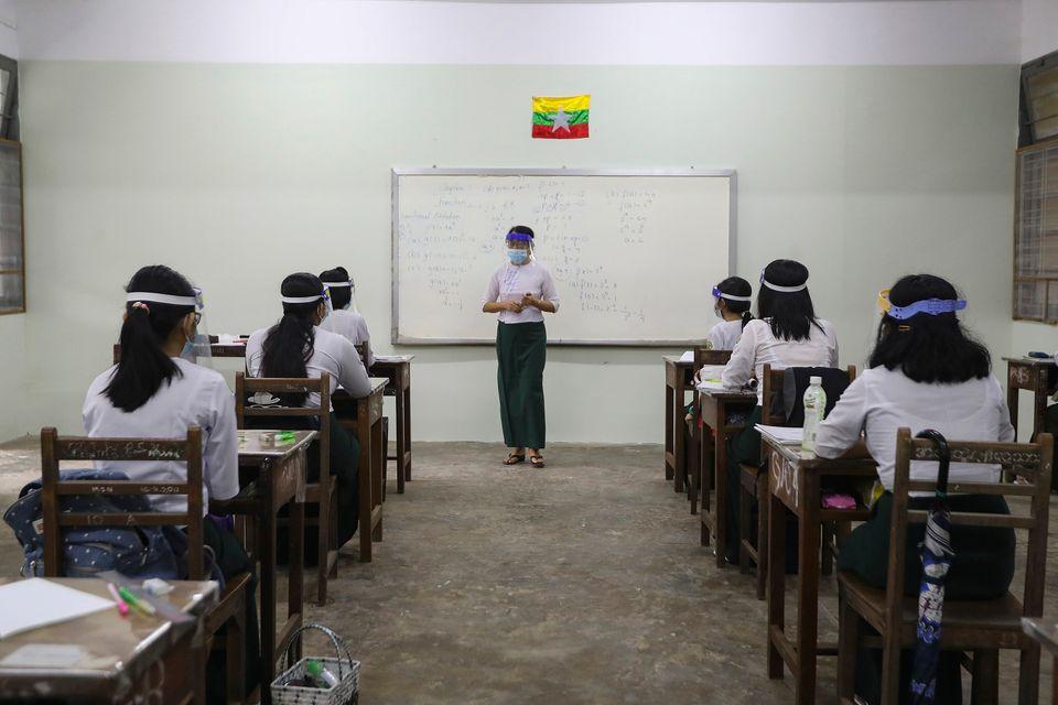 학생들과 교수 모두 마스크와 얼굴가리개를 착용한 채 수업을 듣고 있다. 양곤, 미얀마. 2020년