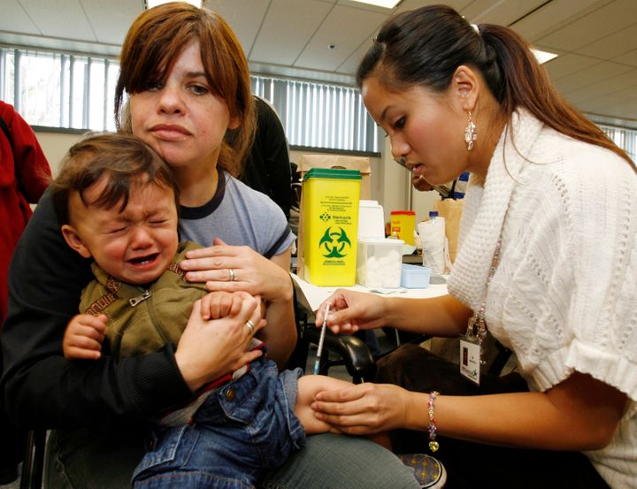 Patricia Steward holds her 11-month son Brayden as he receives his H1N1 pandemic vaccine from a nurse at the The East York Civic Centre clinic in Toronto October 29, 2009. REUTERS/Mike Cassese (CANADA HEALTH)