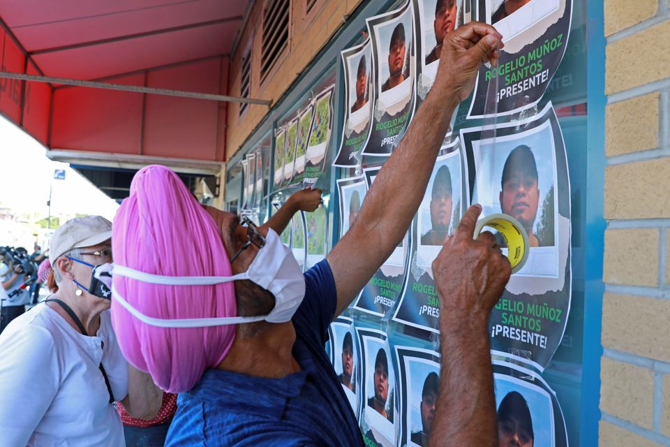Supporters tape photographs of migrant worker Rogelio Munoz Santos, who died from coronavirus disease...