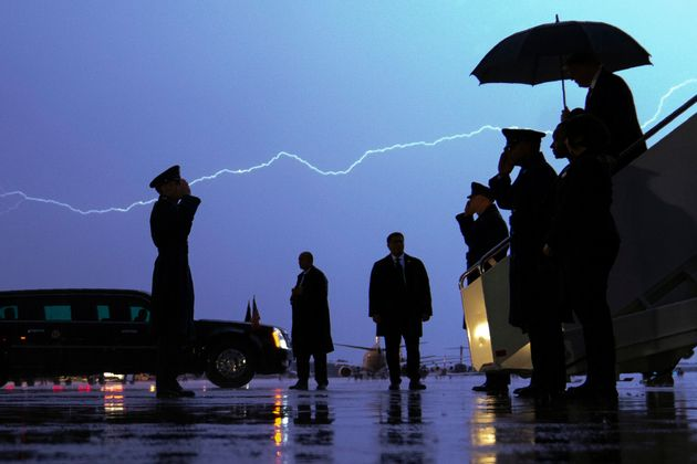 Lightning streaks across the sky as President Donald Trump walks from Air Force One carrying an umbrella...