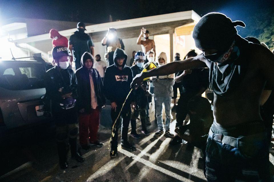Um homem joga bebida alcoólica no local do assassinato de um manifestante antirracista em Kenosha, Wisconsin,...
