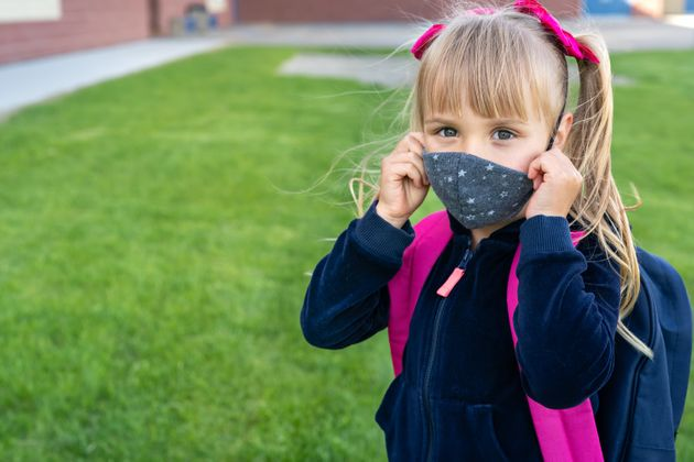 Young student caucasian girl looking at camera and wear protective face mask before school day. Ready...