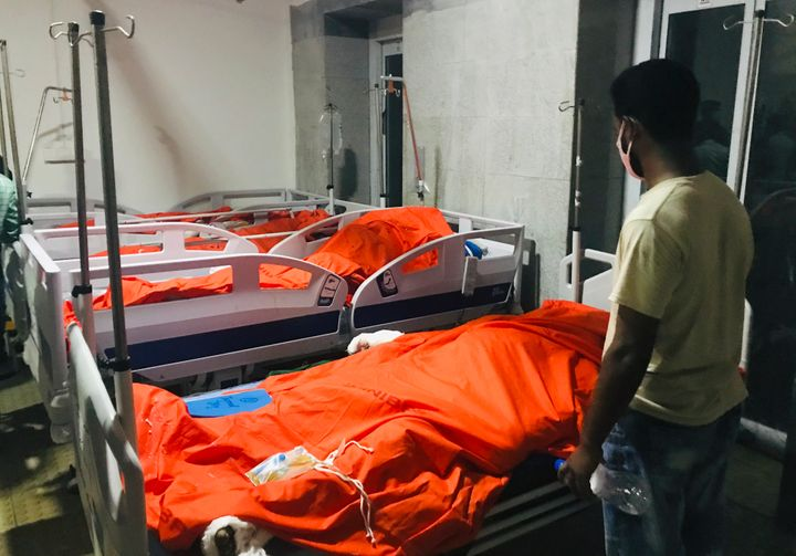 A man stands by the bodies of victims of a gas pipeline explosion at a hospital in Dhaka, Bangladesh, Saturday, Sept. 5, 2020